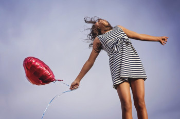 Photo of a woman jumping with heart balloon